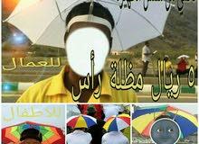 5ريال مظلة رأس تحمي عامل من شمس الظهيرة