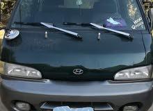 سائق مع باص للنقل بضاعه او مواد