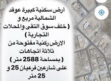 ارض كبيرة للبيع عوقد الشمالية مربع و ركنية 2588 متر خلف سوق التقى