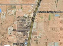 نصف هكتار بيها منزل مساحته 200 متر  المكان العزيزية مقابل مصنع الهريسة طريق اولا
