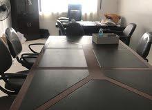 طاولة اجتماعات مع كراسي وطابعة جديدة