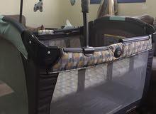 سرير للاطفال ماركة Graco مع مكان لتغيير البيبي وله مستويات للارتفاع شبه جديد بالكرتونه