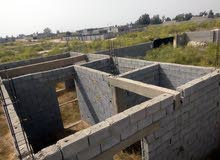 قطعة ارض بها هيكل لمبنى صغير بالقيو