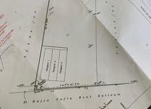 أرض للبيع مساحتها هكتار ونصف محاطة بصور وتحتوي على مستودعات جهة برشيد