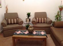غرفة جلوس مع طاولتين وبرادي