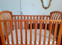 سرير اطفال مستعمل فيه درج للملابس من تحت احد الجوانب يركب وينزل حتي يسهل الرضاعة