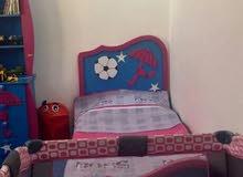 غرفة نوم اطفال مستعمل نظيف ومرتب مع سجادة زرقاء مناسبة للغرفة وستارة هدية