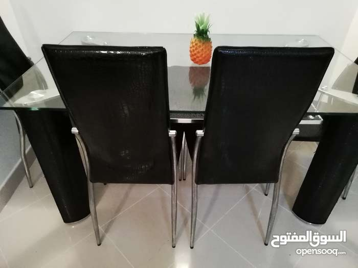 Dinning glass table and 5 chairs, leather, original price bought for 950Aed Duba