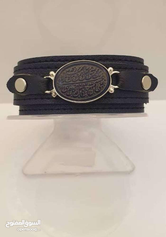 اسورة جلد رجالي بتصميم اوستيك الساعة يتوسطها حجر العقيق الخراساني